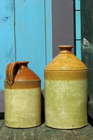 Two antique stoneware jars on wooden decking with blue and purple painted wood in the background.