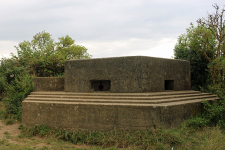 An FW322 type world war two pillbox on the east coast of England with two loopholes and surrounded by trees and shrubs with a grey blue sky.
