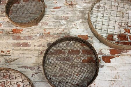 Four vintage metal gardening sieves or riddles hanging on a white washed red brick wall. Фото со стока