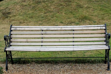 Black painted metal framed seat with ornate ends and wooden slats on the edge of a gravel path with a grass lawn in the background. 스톡 콘텐츠