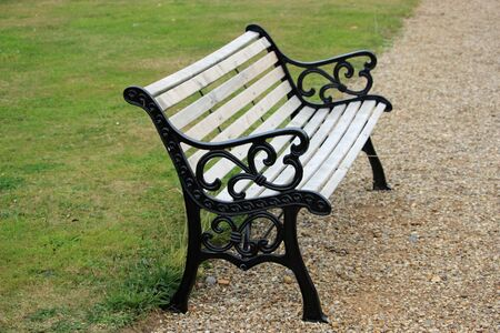 Black painted metal framed seat with ornate ends and wooden slats on the edge of a gravel path with a grass lawn in the background. 写真素材 - 130088674