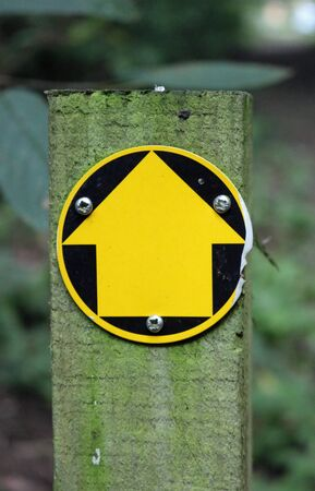 Damaged public footpath sign of a yellow arrow on a black plastic disk screwed to a wooden post with a blurred background of leaves.