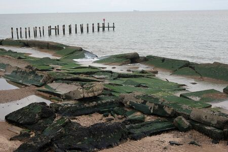 Damaged concrete sea defences on sandy beach north of Lowestoft, Suffolk on England east coast, covered in algae. Sea and breakwater in background.