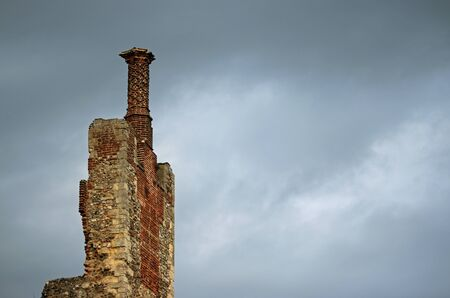 Tudor twisted barley sugar chimney pot on chimney stack with flint, red brick and stone work with a background of grey cloud with good copy space. Stock Photo