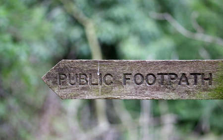 Routed wooden rustic public footpath fingerboard sign pointing to the left with letters not inlaid and a blurred background.