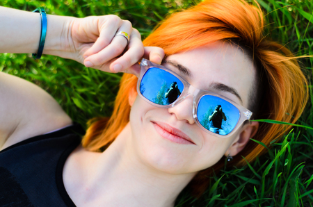 wearing spectacles: The beautiful girl with red hair and wearing spectacles lies poses lying on a grass.The model.
