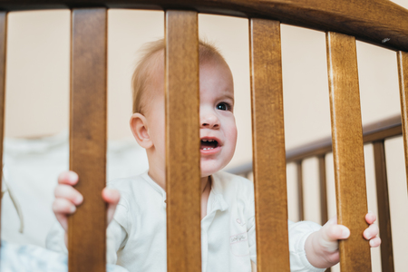 surprised kid: Surprised kid looks at the photographer while standing in crib