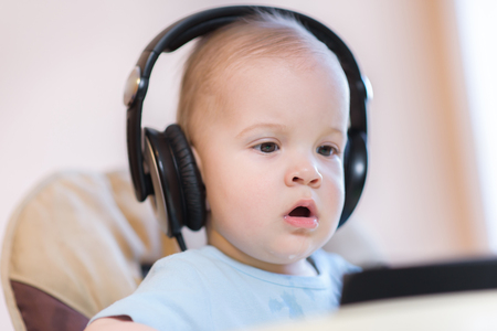 child listening to music on headphones at home Stock Photo