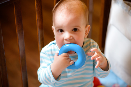 little boy playing with a toy in the crib Stock Photo
