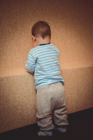 facing a wall:  small child standing facing a wall in the apartment