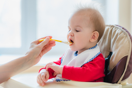 small child sits on a chair and eating with spoon Stock Photo