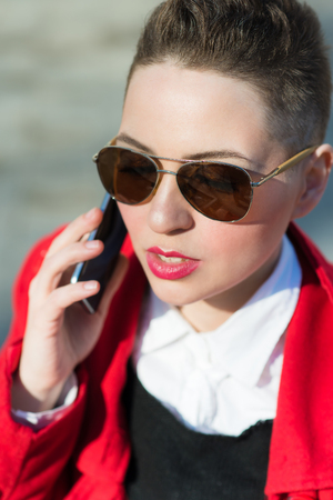 Model with phone on blurred background during the day Stock Photo