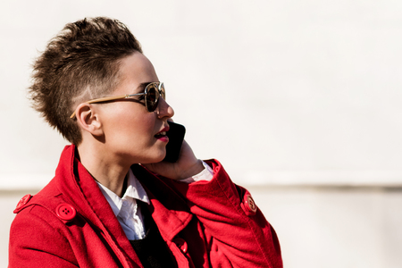 eighties: Model with phone on blurred background during the day Stock Photo