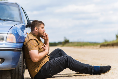 alarmed: Alarmed driver calls the help desk by phone Stock Photo