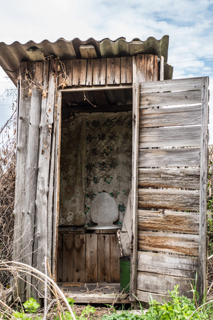 Old wooden rotting toilet in the yard
