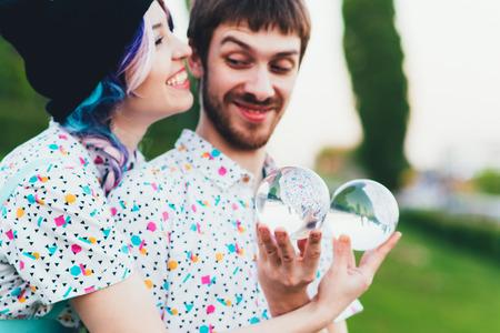 Man and woman juggle with large transparent balls