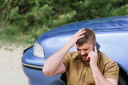 Alarmed driver calls the help desk by phone Stock Photo