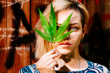 Beautiful girl with a cannabis leaf near the face 版權商用圖片