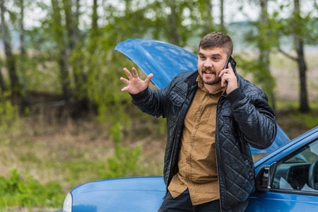 auto repair: Alarmed driver calls the help desk by phone Stock Photo