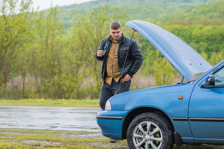 Man smokes near a car on the road