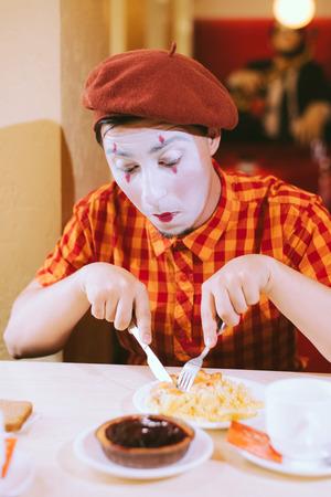 pantomima: Mime come pastel en una cafetería y hace una mueca