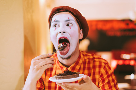 Mime eats cake in a cafe and croaks a face