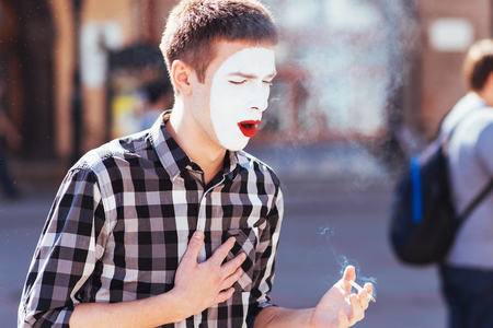 man mime smokes a cigarette in town