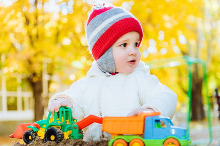the kid plays cars in the sandbox on the street Stock Photo