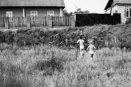 Deux soeurs courent à la maison dans le village Banque d'images - 91050362