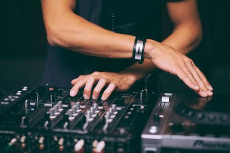 DJ controls a remote at a club party 写真素材