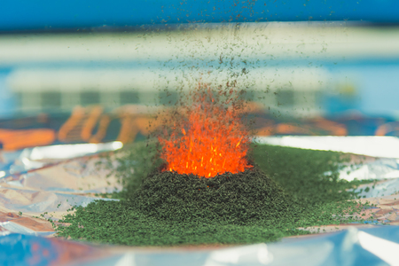 chemical reaction of ammonium dichromate if to set fire to it on the foil Stock Photo