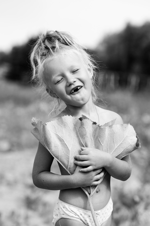 little toothless village girl posing under a burdock