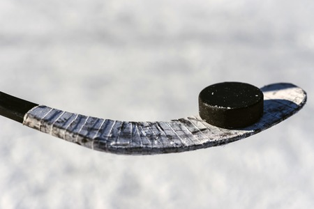 close-up stick and puck on the ice background