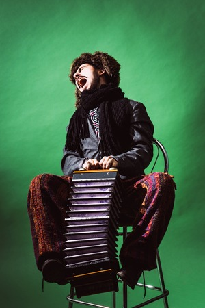 positive man with accordion posing in studio