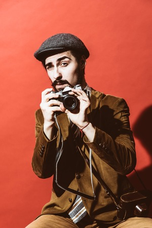 very positive photographer posing in studio with camera