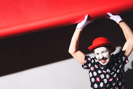 cheerful mime picks up the background and grimaces in the studio Zdjęcie Seryjne