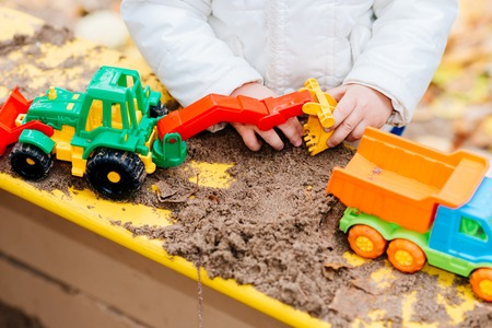 the kid plays cars in the sandbox on the street Banque d'images