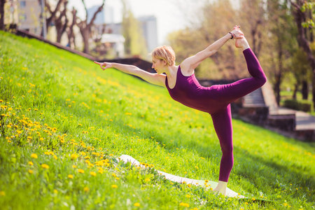beautiful girl engaged in yoga on green grass on a sunny day