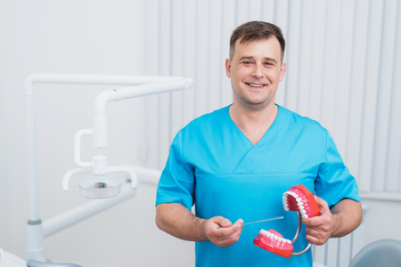 Doctor Orthodontist showing your teeth how to care for your teeth