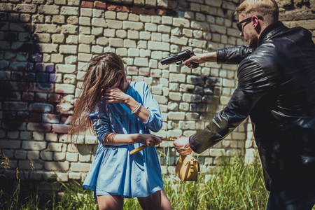the robber on the street threatens the girl with a pistol and wants to take her bag from her. Stock Photo