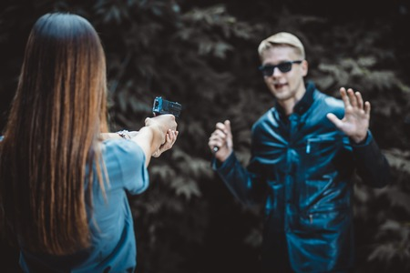 girl with a gun holds on the sight of the criminal with a knife in his hand. The thug wants to attack a woman Stock Photo