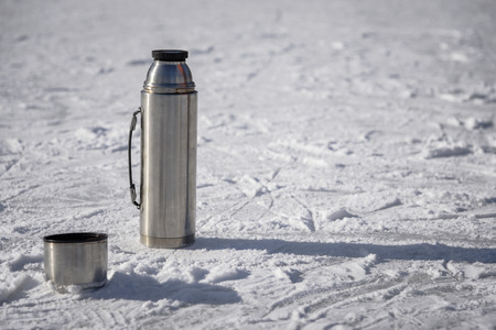an open vacuum flask stands on ice with a cup of hot tea Banque d'images