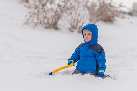 A little boy is digging snow with a shovel in the winter outside.