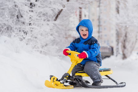 little boy rides a snow scooter in winter Standard-Bild