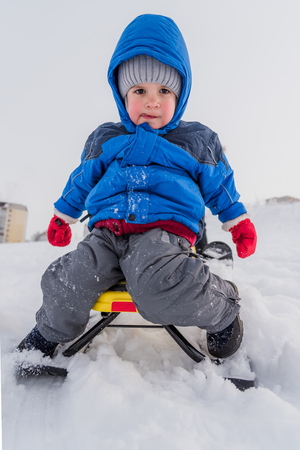 little boy rides a snow scooter in winter Banque d'images