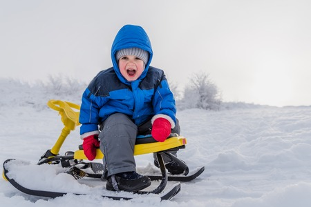 little boy rides a snow scooter in winter