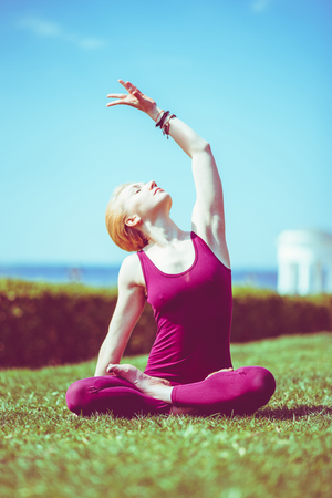 cute girl meditating in lotus position sitting on grass on sunny day