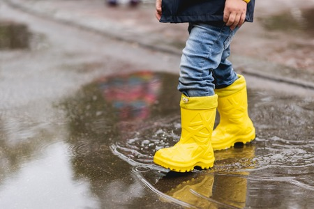 cute baby walks through the puddles in the spring in the city