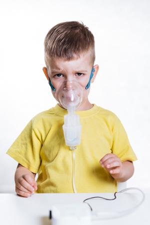 little boy treats cough by inhaler at home