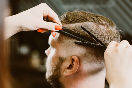 girl hairdresser cuts scissors bearded man in the salon Banque d'images - 123972240